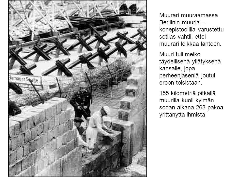 Muurari muuraamassa Berliinin muuria – konepistoolilla varustettu sotilas vahtii, ettei muurari loikkaa länteen.